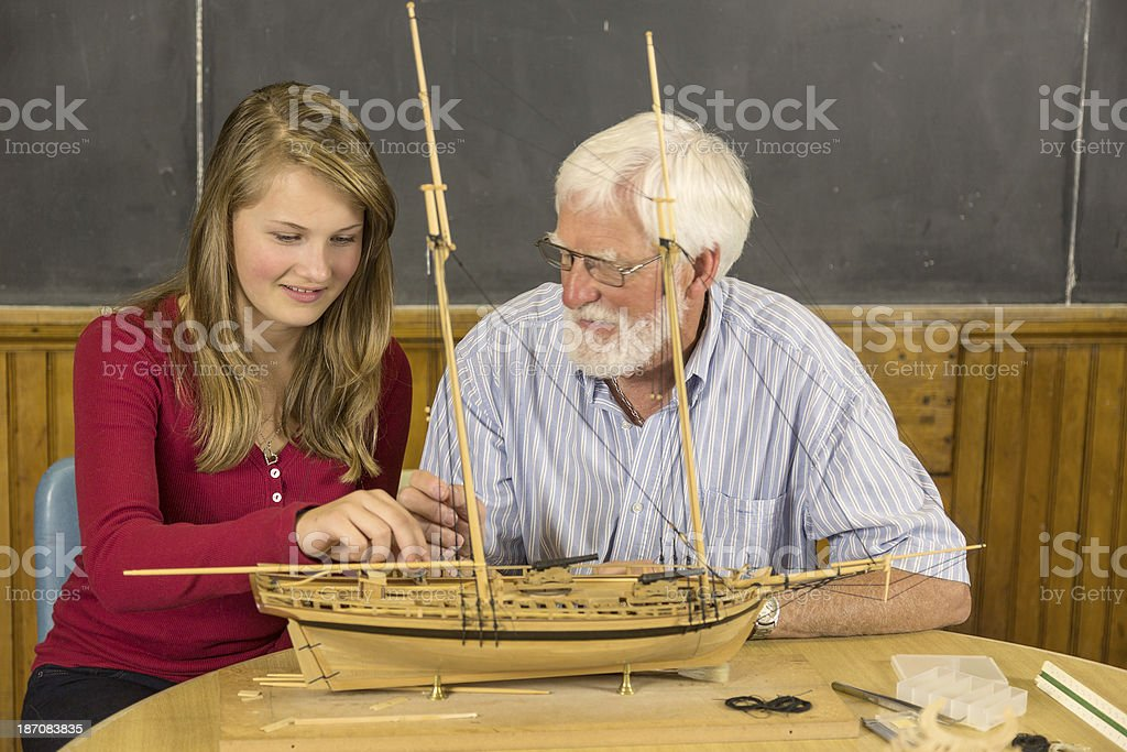 Grandfatther with grandaughter building modelship. royalty-free stock photo