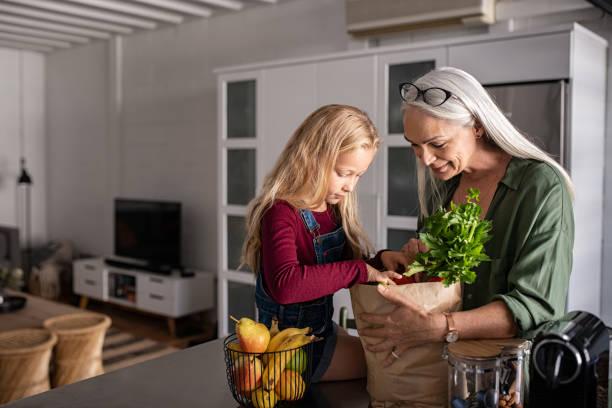grandma and girl holding grocery shopping bag - comida sustentavel imagens e fotografias de stock