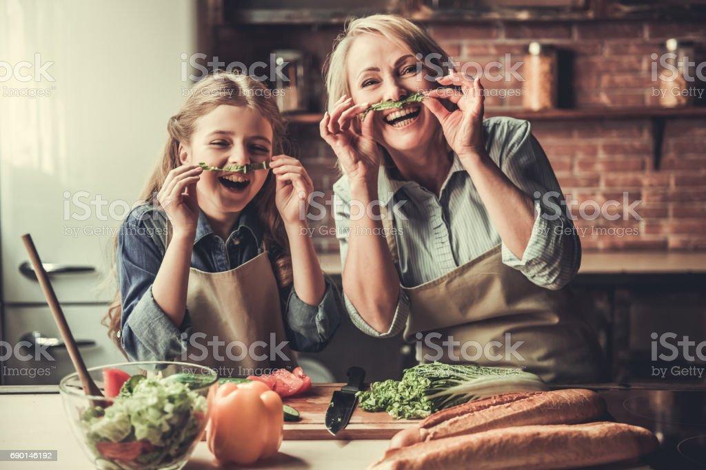 Grandma and granddaughter in kitchen stock photo