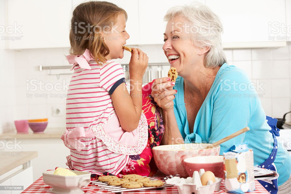 Grandma and Granddaughter laugh and bake cookies stock photo