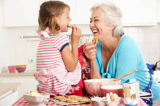 grandma and granddaughter laugh and bake cookies - granddaughter and grandmother stock photos and pictures
