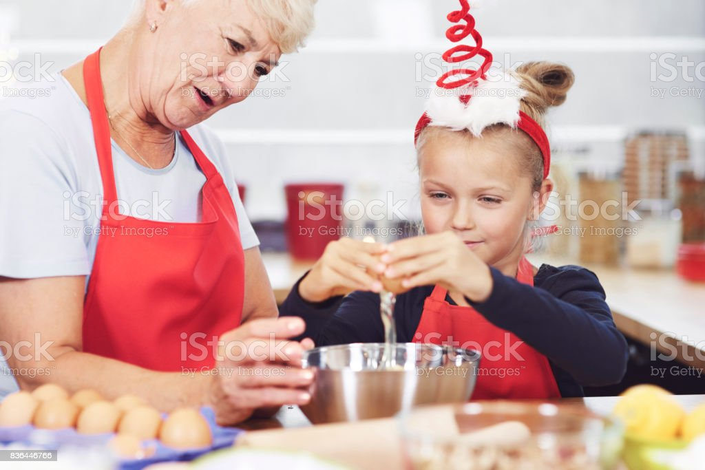 Grandma and granddaughter preparing snack in kitchen stock photo