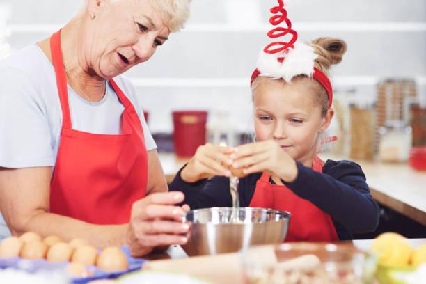 Grandma and granddaughter preparing snack in kitchen stock photo