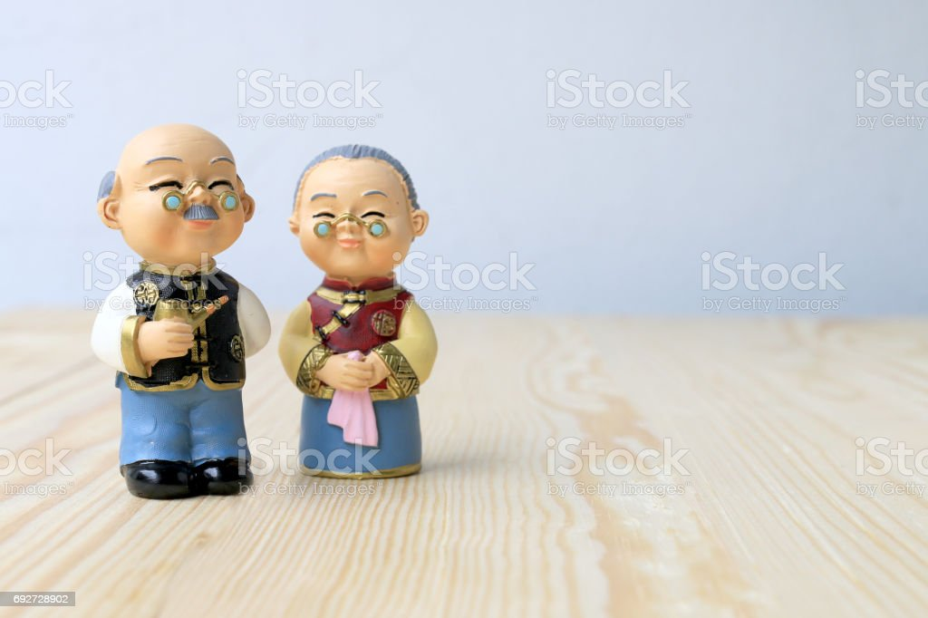 Grandma and grandpa dolls in chinese uniform style standing on wooden background. in chinese new year stock photo