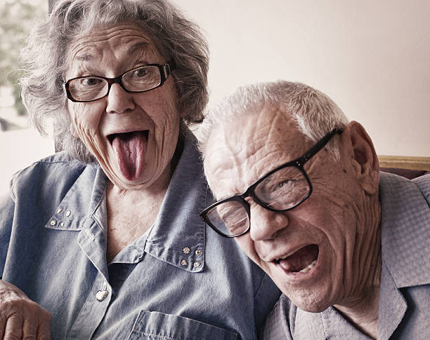 Grandma and Grandpa Making Funny Tongue Wagging Faces A crazy, fun-loving elderly octogenarian senior adult married husband and wife couple sitting together in a restaurant are making silly funny tongue wagging faces. Both Grandma and Grandpa are playful and laughing - they love mugging for the camera. Desaturated. desaturated stock pictures, royalty-free photos & images