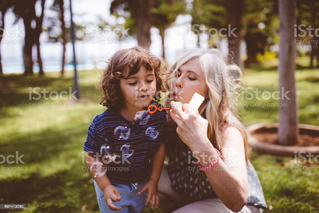Grandma and grandson blowing bubbbles in a garden at summer stock photo