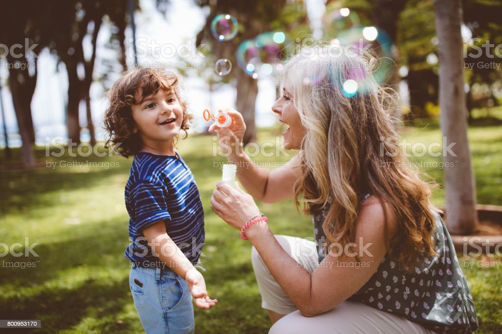Grandma and grandson laughing and blowing bubbles at the park stock photo