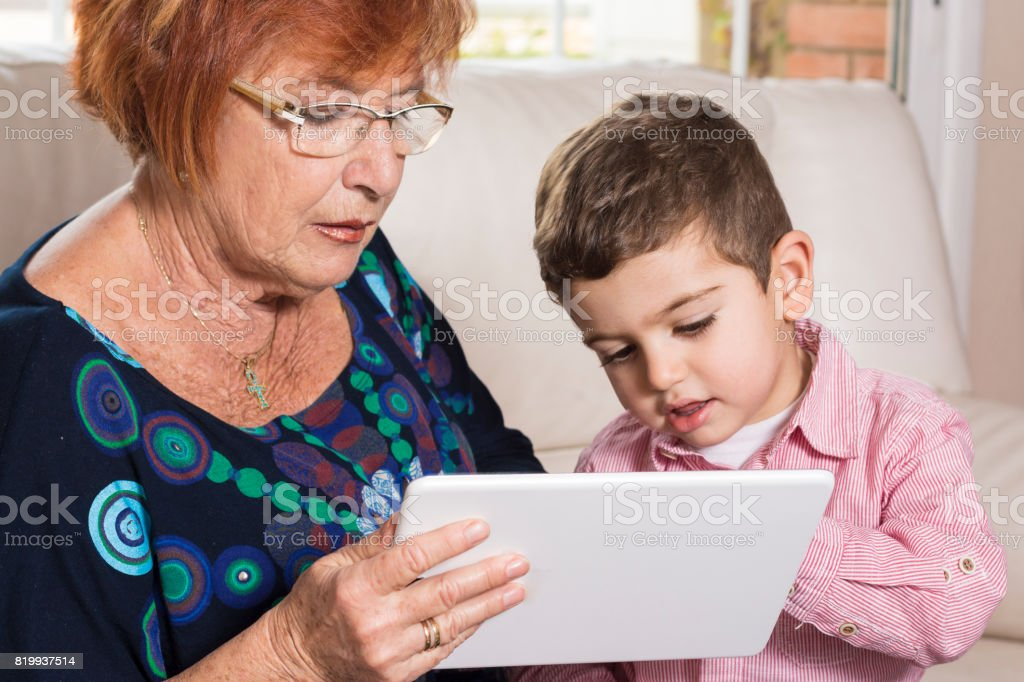Grandma and grandson looking at tablet computer together stock photo