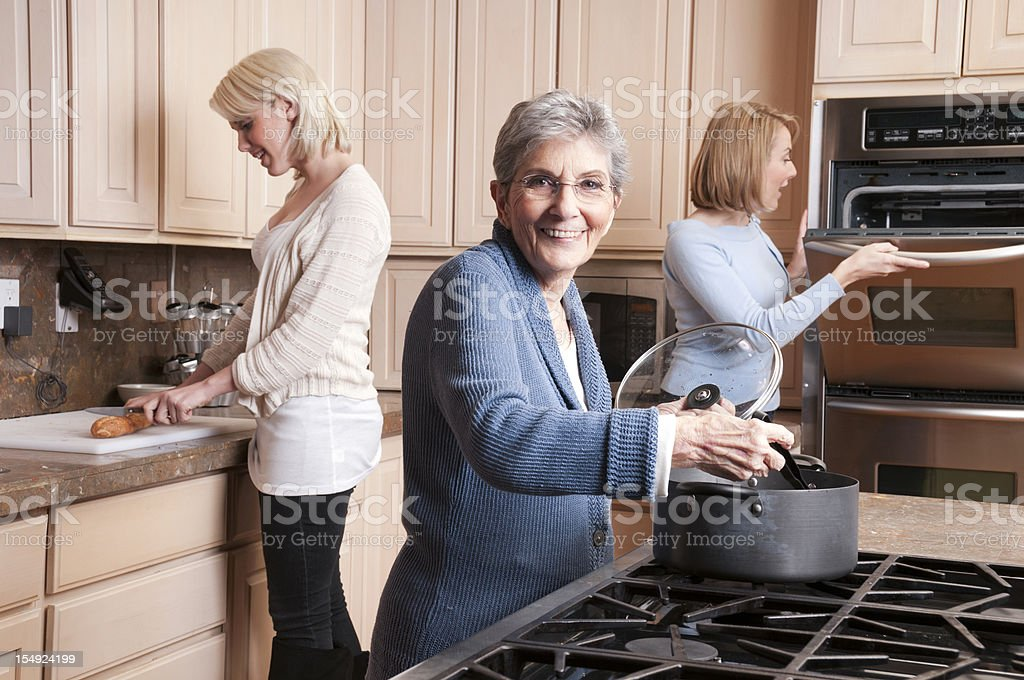 Grandma Cooking with Daughter and Grandaughter stock photo