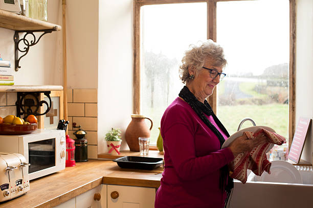grandma drying dishes - independence stock photos and pictures