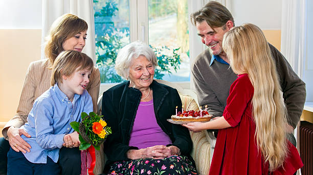 Grandma gets a birthday cake. Grandma gets a birthday cake from loving family. birthday wishes for daughter stock pictures, royalty-free photos & images