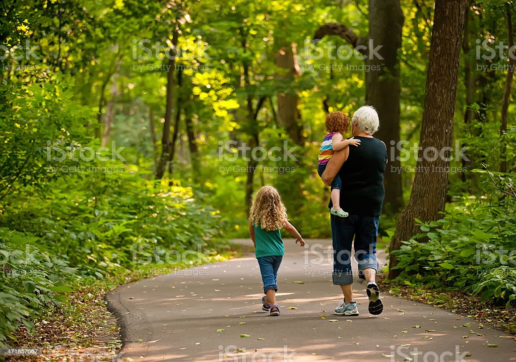 Grandma & Graunddaughters Walking on Park Trail stock photo