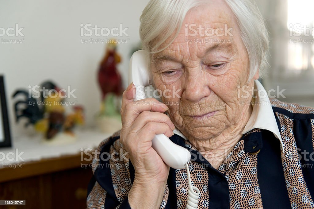 Grandma is holding a phone in hand and looks sad stock photo