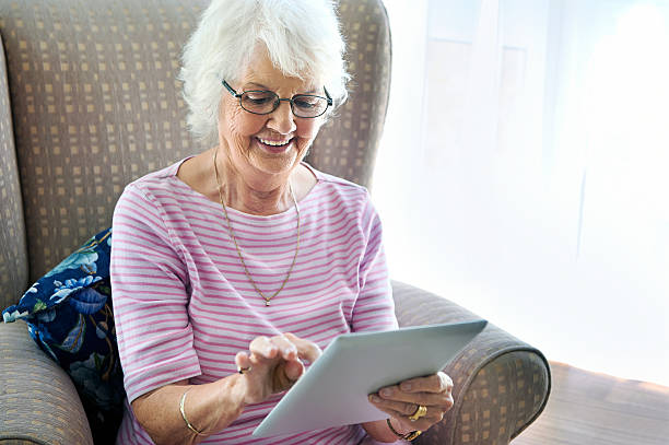 grandma learning tablet stock photo