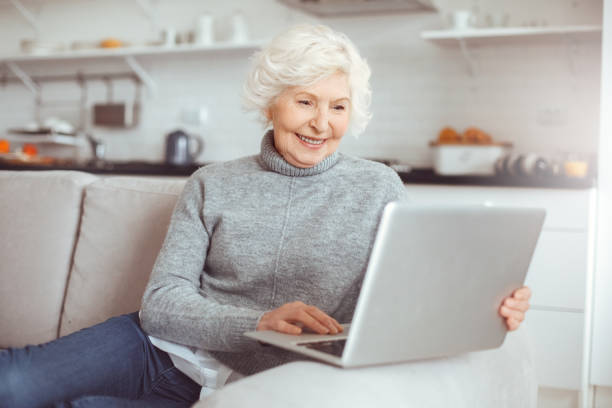 Grandma learns how to work with a computer at home stock photo