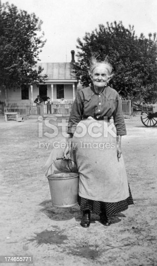 My great great great grandmother on a old farm holding a bucket of water.