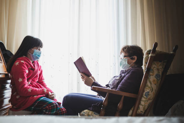 Grandma reading a book for her little grandaughter at home. stock photo