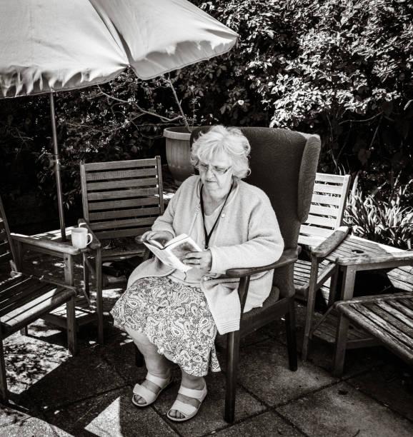Grandma reading in the back garden, Black and white, Southampton, UK stock photo