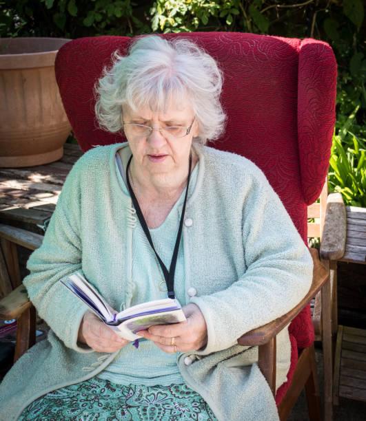 Grandma reading in the garden, Southampton, UK stock photo