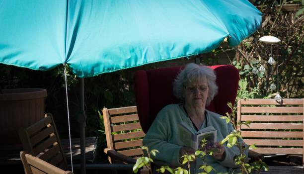 Grandma reading in the garden under the parasol stock photo
