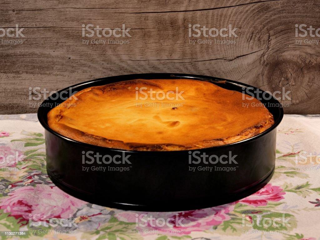 Oma s Käsekuchen, frisch gebacken, noch in die Auflaufform auf eine Tischdecke Hintergrund Holz – Foto