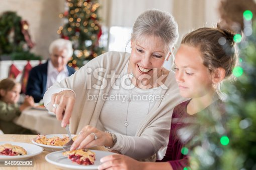 Attractive senior woman serves her young granddaughter a slice of cherry pie after their Christmas meal.