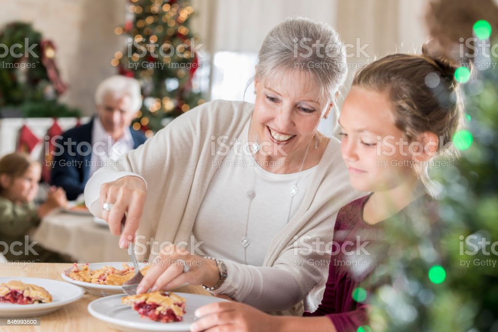 Grandma serves her granddaughter a slice of pie stock photo