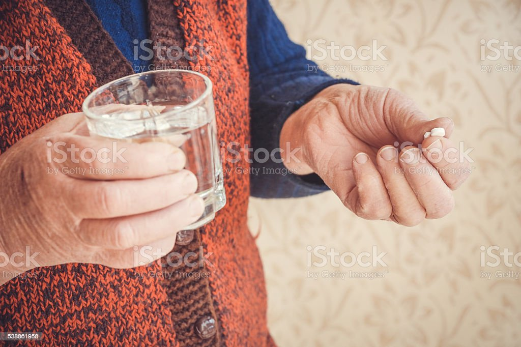 Grandma taking pills with a glass of water stock photo