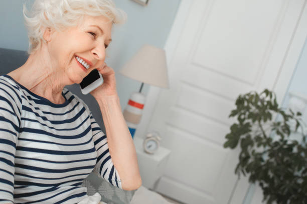 Grandma talking to family on the phone in the morning stock photo