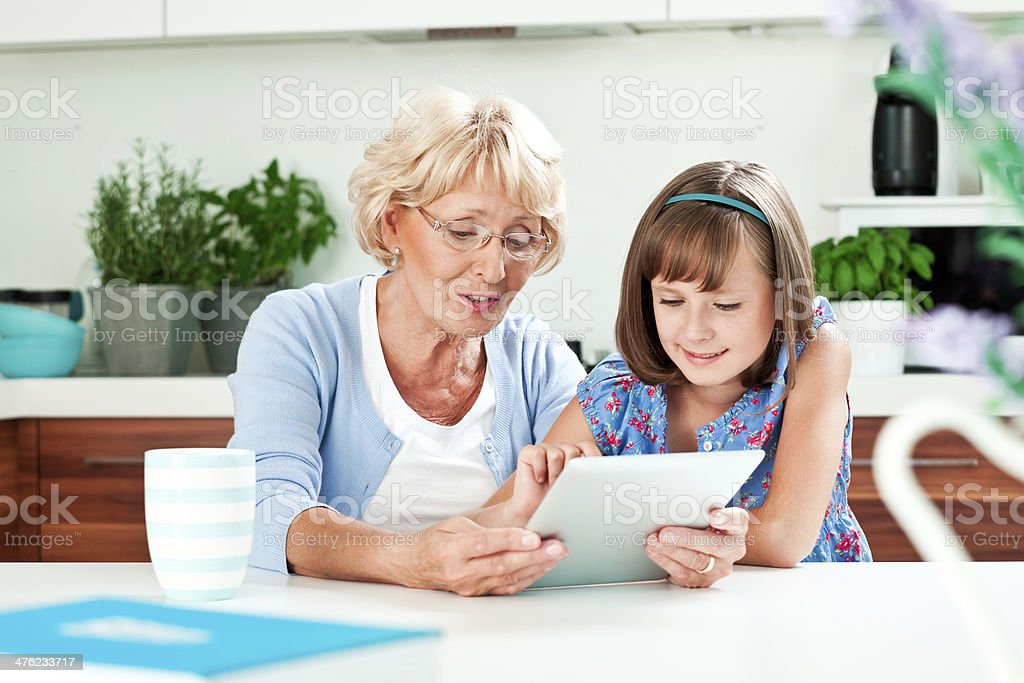 Grandma using digital tablet with grandchild royalty-free stock photo