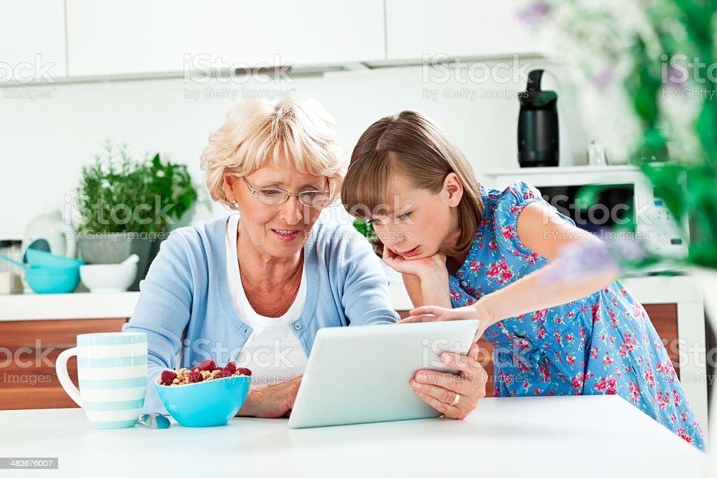Grandma using digital tablet with grandchild royalty-free stock photo