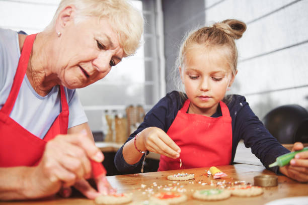 Grandma with girl applying icing on cookies stock photo