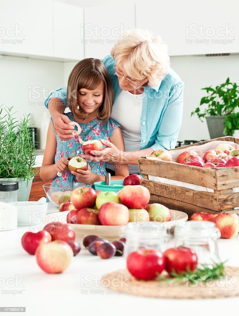 Grandma with granddaughter peeling apples royalty-free stock photo