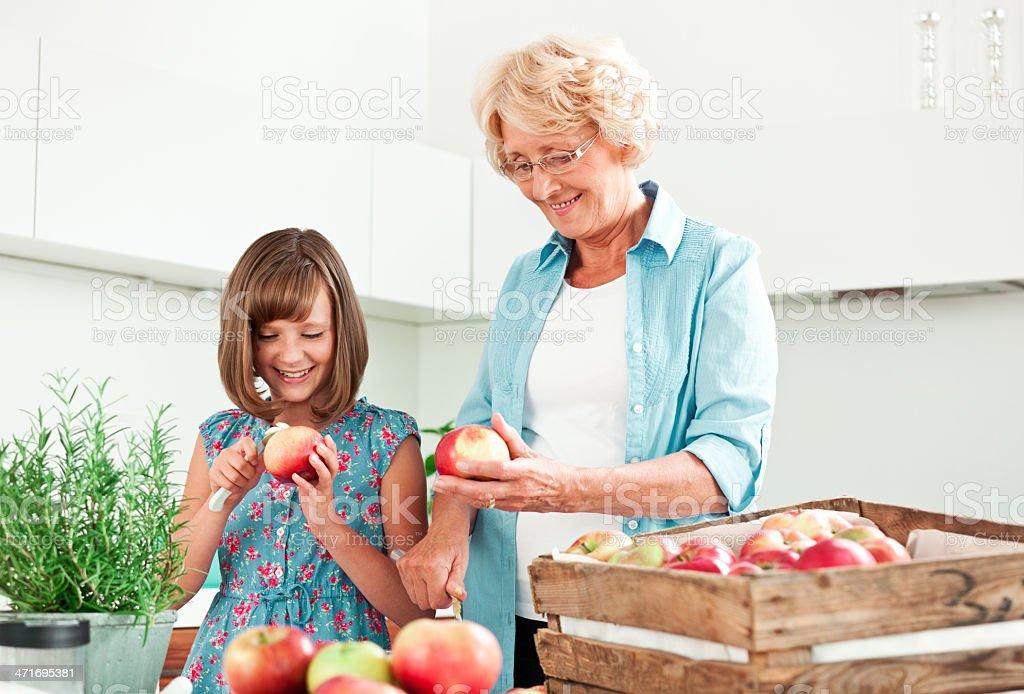 Grandma with granddaughter peeling apples royalty-free stock photo