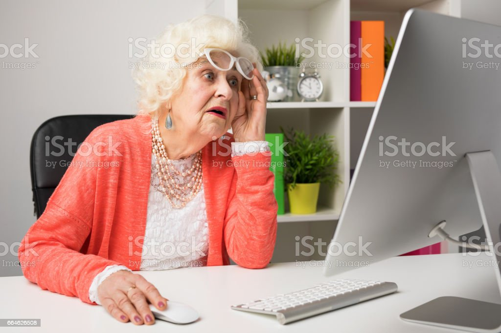 Grandma working at the office and looking at the computer in disbelief royalty-free stock photo