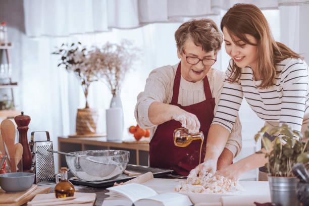 grootmoeder olie toe te voegen aan deeg - oil kitchen stockfoto's en -beelden
