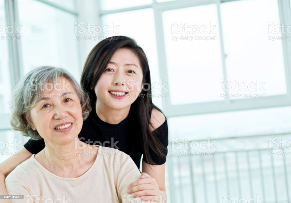 Grandmother and adult granddaughter hugging together at home stock photo