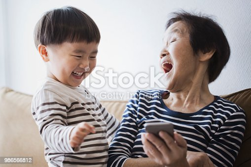 An asian senior woman and her grand son using a smartphone together.