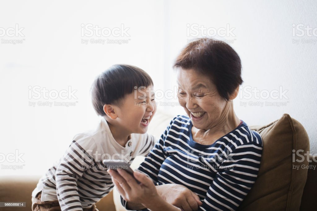 Grandmother and boy using  a smart phone together at home stock photo