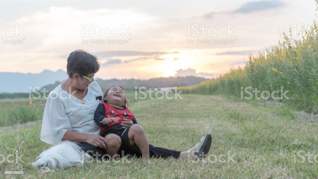 Grandmother and daughter with happy family enjoying life together at meadow. stock photo