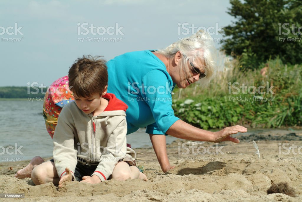 Grandmother and grandchild playing on the beach 2 royalty-free stock photo