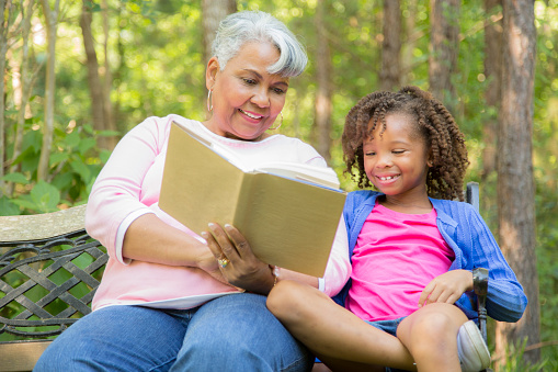 Grandmother And Grandchild Reading Books Outdoors Together Stock ...