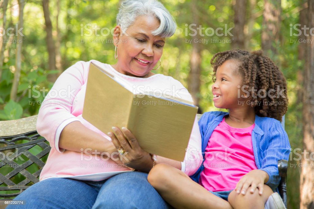 Grandmother and grandchild reading books outdoors together. royalty-free stock photo