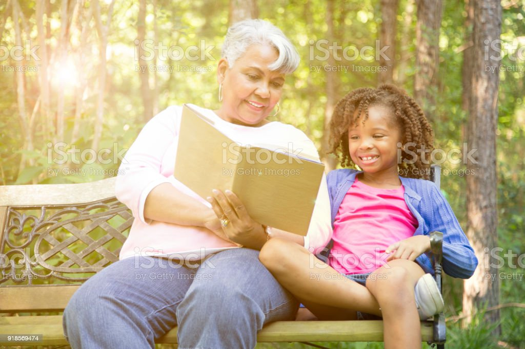 grandmother and grandchild reading books outdoors together stock