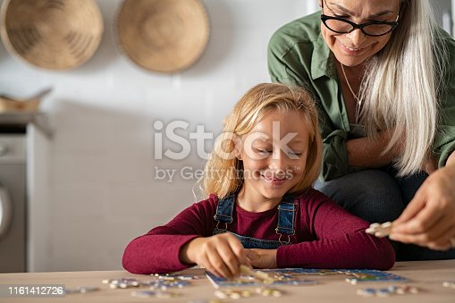 istock Grandmother and grandchild solving jigsaw puzzle 1161412726