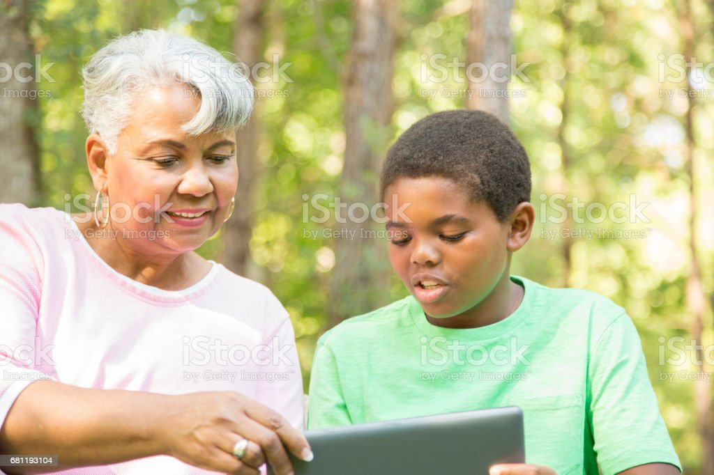 Grandmother and grandchild using digital tablet outdoors together. royalty-free stock photo