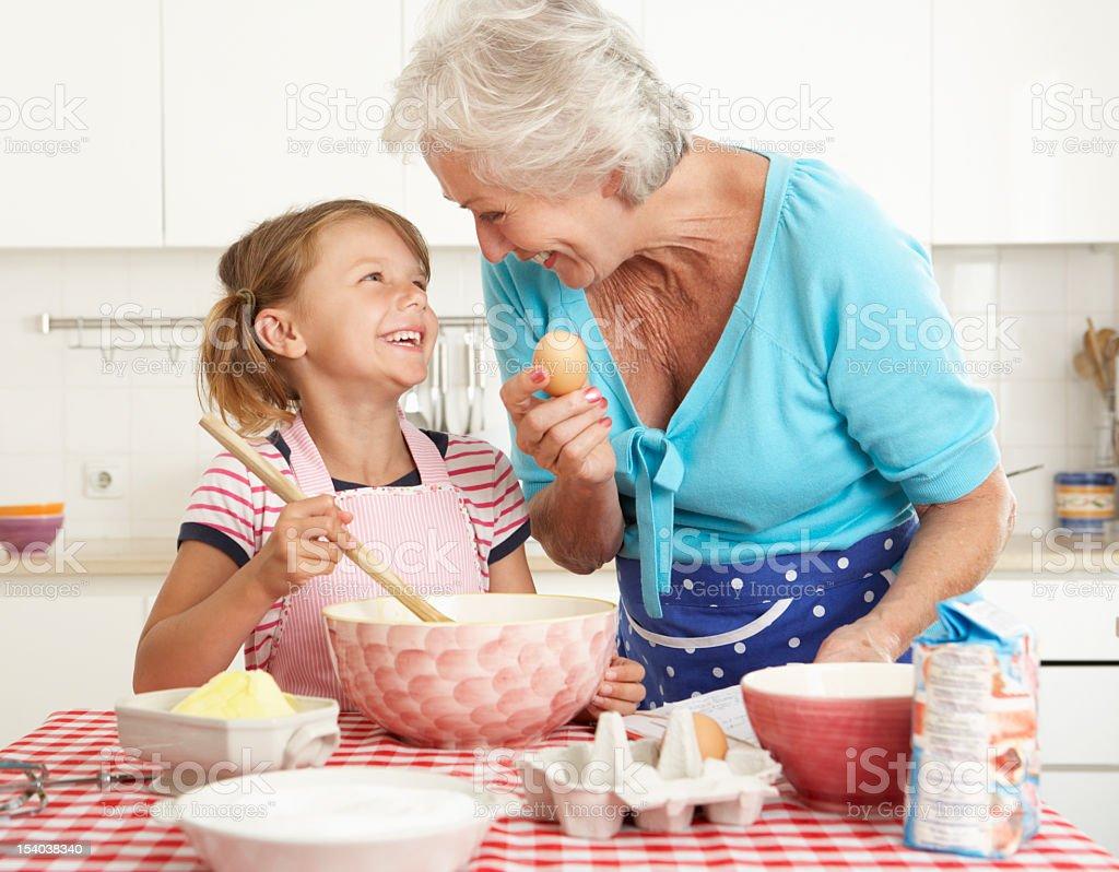 Abuela y Granddaughter cocinar en la cocina - foto de stock