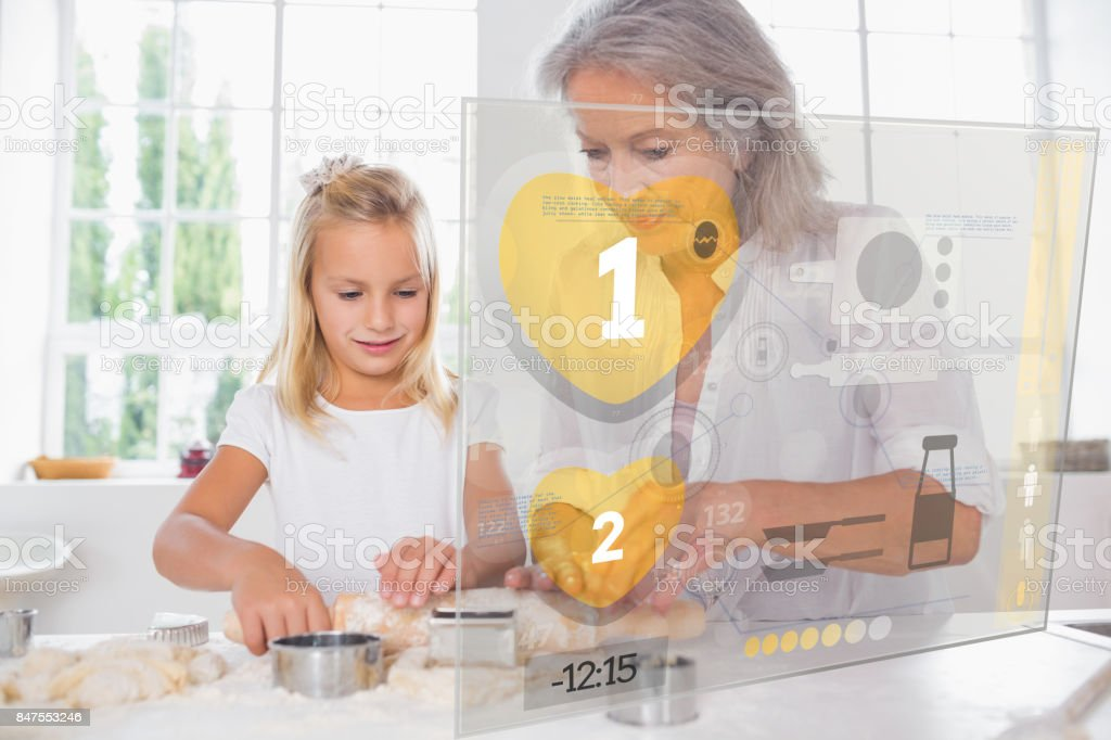Grandmother and granddaughter baking with interface stock photo