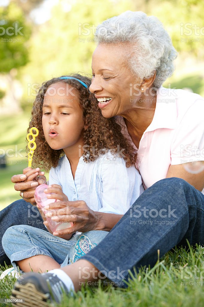 Grandmother And Granddaughter Blowing Bubbles In Park royalty-free stock photo
