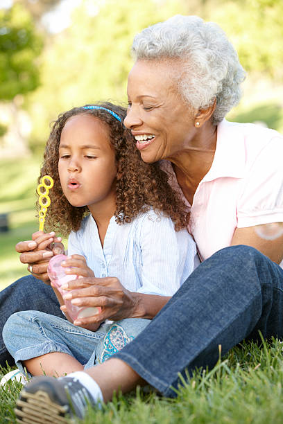 Grandmother And Granddaughter Blowing Bubbles In Park stock photo